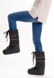 Flicka i varm månekängor och jeans på en vit bakgrund Royaltyfri Fotografi
