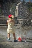 Flicka i varm sommarstad med vattenspridaren Arkivfoton