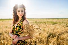 Flicka i vetefält bukett av vete i hand för natursommar för härlig afton varm solnedgång mycket royaltyfri foto