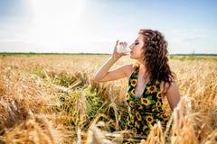 Flicka i vetefält Flickan häller mjölkar in i ett exponeringsglas royaltyfria bilder