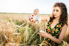 Flicka i vetefält Flickan häller mjölkar in i ett exponeringsglas arkivbild