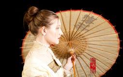 Flicka i viktoriansk klänning i profil med det kinesiska paraplyet Arkivbild
