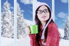 Flicka i vinterkläder som dricker den varma drycken Arkivfoto