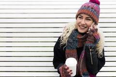 Flicka i vinterkläder som dricker kaffe Royaltyfri Foto