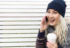 Flicka i vinterkläder som talar på telefonen och skratta Arkivbilder
