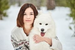 Flicka i vinterskogen som går med en hund Snow faller arkivfoto