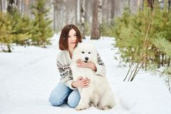 Flicka i vinterskogen som går med en hund Snow faller royaltyfria foton