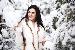 Flicka i vinterskogståenden av en flicka Flickan i vintern går i träna snö häller från filial Arkivbild