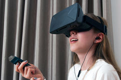 Flicka i virtuell verklighethörlurar med mikrofon och ljudapparaten som ser upp och Royaltyfria Bilder