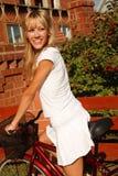Flicka i vit med cykeln Royaltyfri Fotografi
