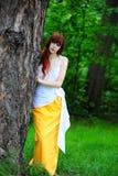 Flicka i vit med en gul aftonklänning vid trädet arkivbild