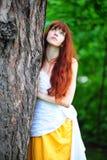 Flicka i vit med en gul aftonklänning vid trädet royaltyfri foto
