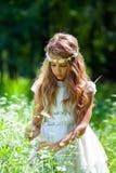 Flicka i vita klänningplockningblommor. arkivbilder