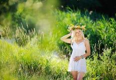 Flicka i vita sundress och en krans av blommor på hennes head aga Royaltyfri Bild
