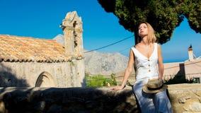 Flicka i vitt klänningsammanträde nära en gammal kyrka arkivfoto