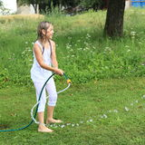 Flicka i vitt plaska med den trädgårds- slangen Arkivfoton