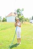 Flicka i vitt plaska sig med den trädgårds- slangen Arkivfoto