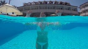 Flicka i vitt simma för baddräkt som är undervattens- i pölen stock video