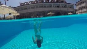 Flicka i vitt simma för baddräkt som är undervattens- i pölen lager videofilmer