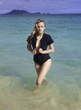 Flicka i wetsuit på stranden Arkivbild