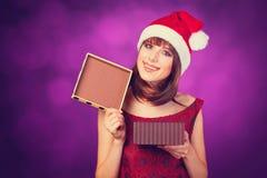Flicka i xmas-hatt med gåvaasken arkivfoto