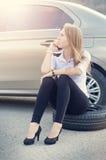 Flicka kalla Bruten bil på en bakgrund Kvinnan sitter på ett hjul Sexig reparation för ung kvinna en bil Naturlig bakgrund Bilacc Royaltyfria Bilder