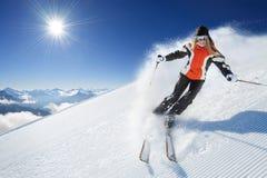 Flicka/kvinna/kvinnligt på skida på den soliga dagen