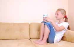flicka little hålla ögonen på för tv Arkivfoto