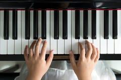 flicka little leka för piano arkivfoto