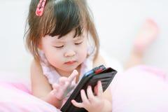 flicka little mobilt använda för telefon Fotografering för Bildbyråer