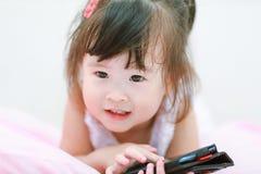 flicka little mobilt använda för telefon Arkivbild