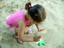 flicka little sandlåda Arkivbilder