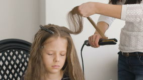 flicka little som är olycklig Mamman eller barberaren flätar henne flätade trådar för härligt brunt lockigt sund isolerad pink fl arkivfilmer