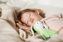 flicka little som sovar Bekymmerslös sömn behandla som ett barn lite med en mjuk leksak Fotografering för Bildbyråer