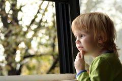 flicka little som ut ser fönstret royaltyfri bild