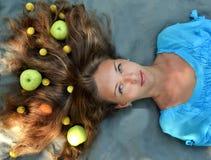Flicka med äpplen i hennes hår Arkivbild
