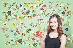 Flicka med äpplet och frukter, gräsplan arkivfoton