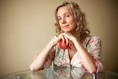 Flicka med äpplet som sitter på tabellen Royaltyfria Bilder