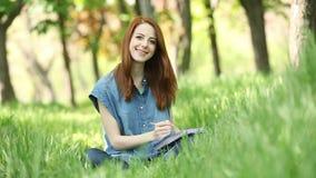 Flicka med anteckningsboken lager videofilmer