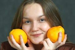Flicka med apelsiner Arkivbild