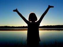 Flicka med armar som lyfts av sjön Arkivfoto