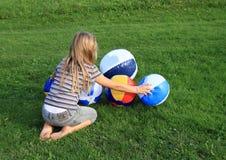 Flicka med att blåsa upp bollar arkivfoto