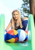 Flicka med att blåsa upp bollar på glidbana Arkivbild