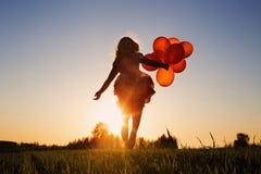 Flicka med att hoppa för ballonger Royaltyfria Foton