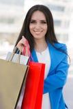 Flicka med att le för shoppingpåsar Royaltyfri Foto