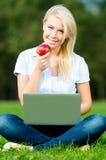Flicka med bärbar dator- och äpplesammanträde på det gröna gräset arkivfoto