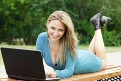 Flicka med bärbar dator som ligger på bänken 图库摄影