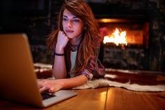 Flicka med bärbar datordatoren som bläddrar på internet royaltyfri bild