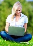 Flicka med bärbar datorsammanträde på gräset royaltyfri foto