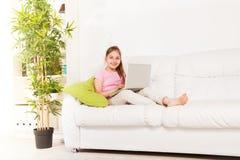 Flicka med bärbara datorn på soffan Arkivbilder